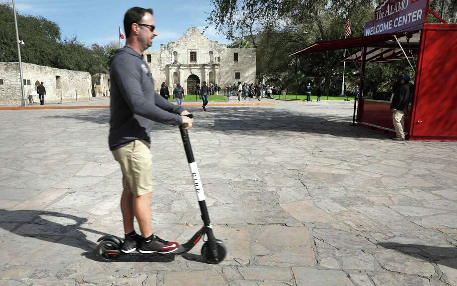 """The new Alamo """"Welcome Center"""", right, sits Feb. 19 where vendors sold snowcones for decades, as a scooter rider rides in Alamo Plaza — which is now against city ordinance. Photo: Bob Owen /San Antonio Express-News / ©2019 San Antonio Express-News"""