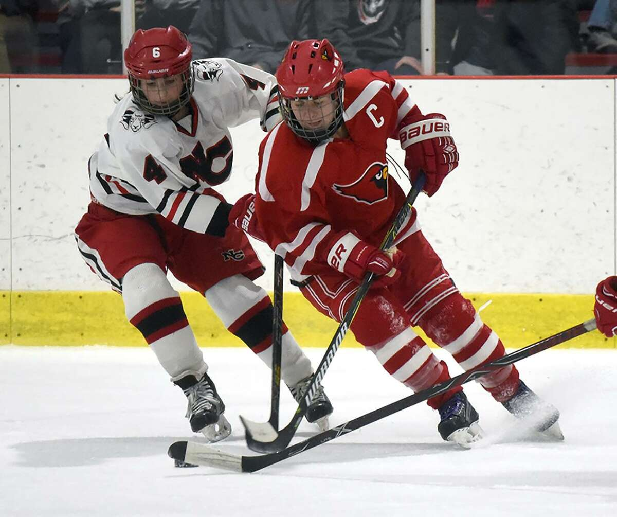 New Canaan's Kaleigh Harden (4) and Greenwich's Jennifer Kelly battle for the puck during a girls ice hockey game at the Darien Ice House on Jan. 18. Kelly, a Greenwich captain, has her eyes set on Darien.