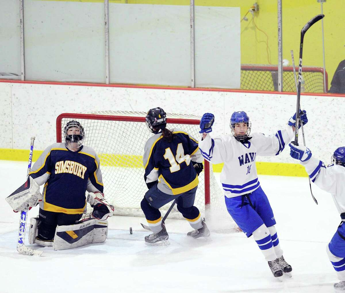 Darien's Shea van den Broek, right, reacts after beating Simsbury goalie Tori LaCroix, left, scoring the first goal of the game for Darien in the first period of the girls high school state hockey playoff game against Simsbury at Terry Conners Ice Rink in Stamford on March 3, 2018. At center is Mackenzie Lynch (14).