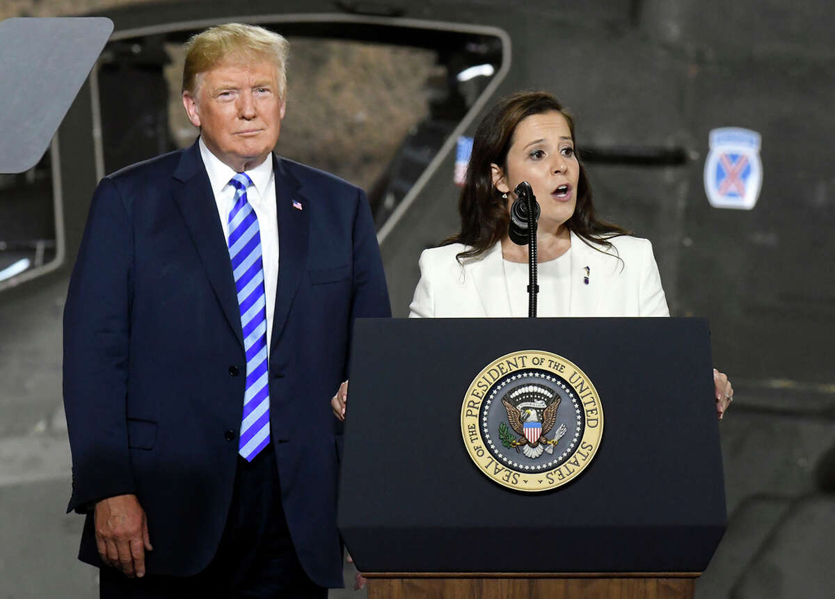 FILE. President Donald Trump, left, listens as Rep. Elise Stefanik, R-N.Y., speaks before signing a $716 billion defense policy bill named for John McCain Monday, Aug. 13, 2018, in Fort Drum, N.Y.