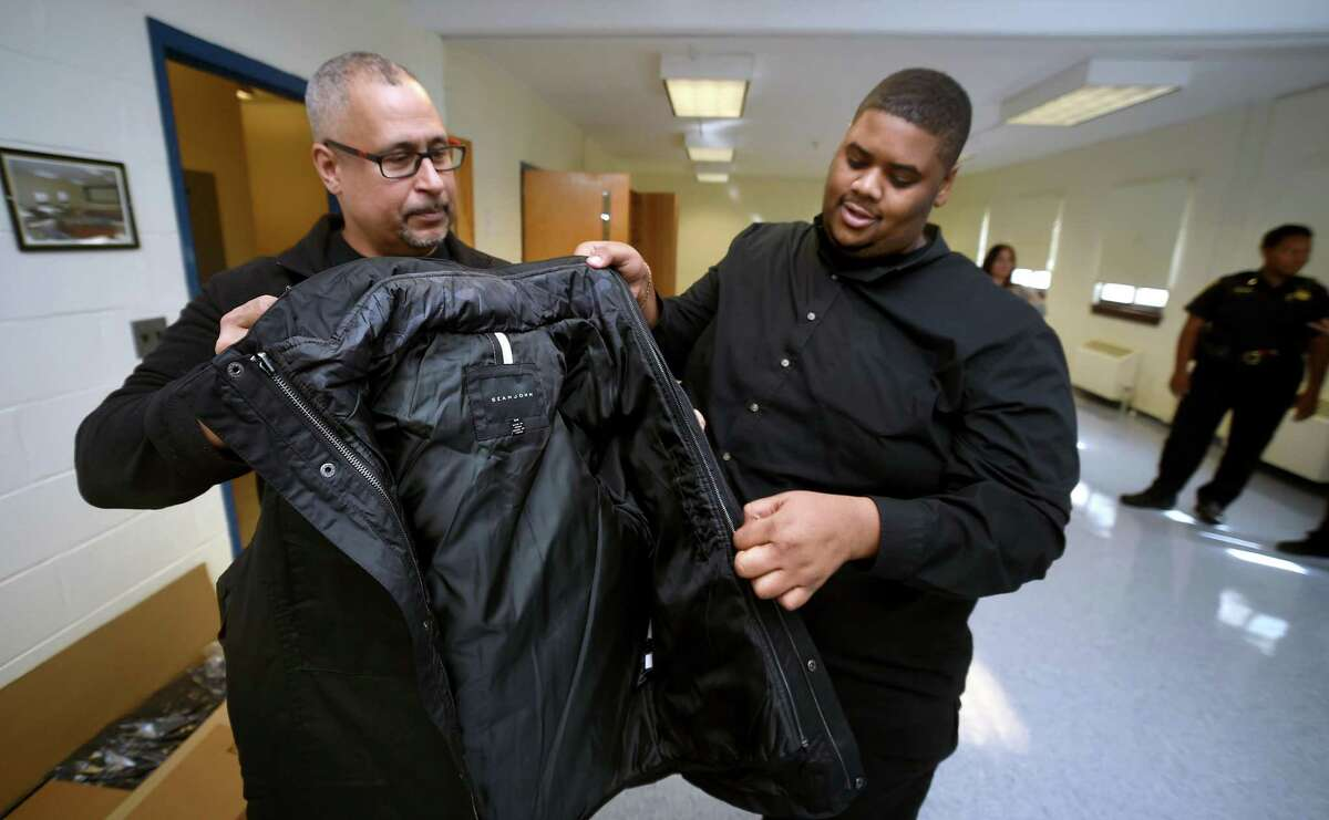 Jason Bartlett (left), director of Youth Services, and Youth Service specialist Ronald Huggins inspect one of the 700 plus coats donated by the Dalio Foundation being stored by the New Haven Police Department on Oct. 16, 2018 for distribution to children in need in New Haven.