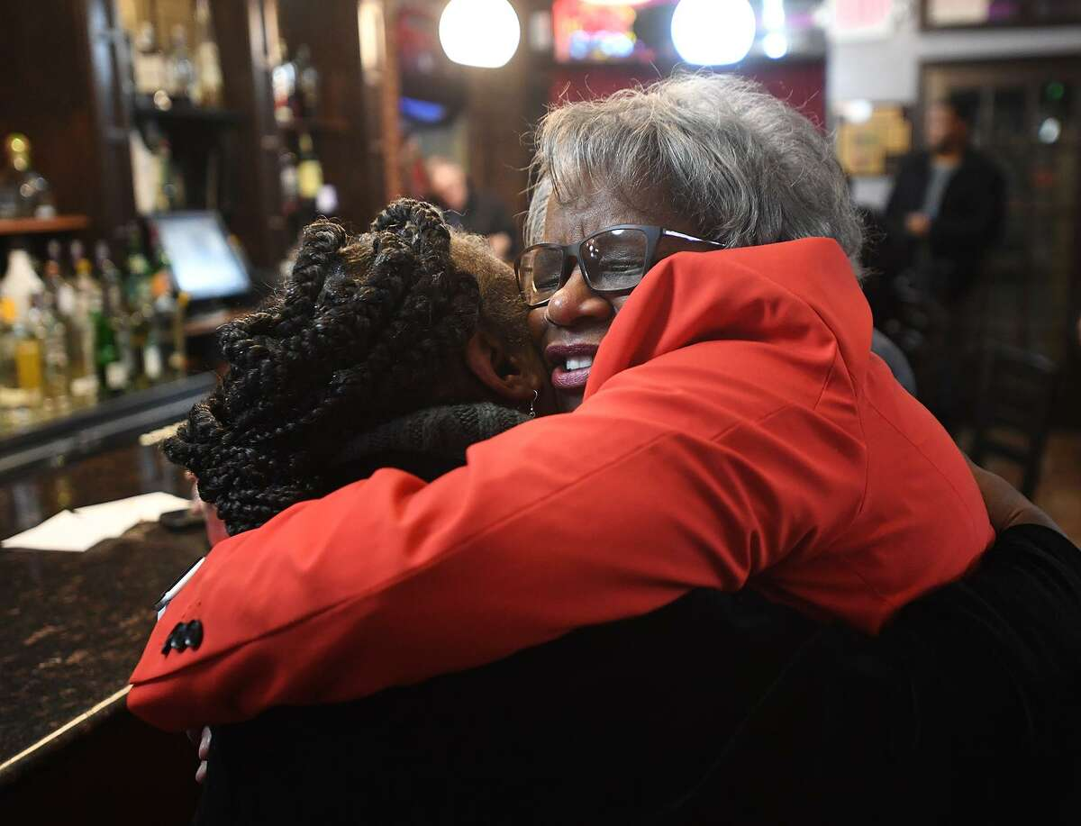 State Sen. Marilyn Moore, right, shares a long hug with former city health director Dr. Marian Evans at her first fundraiser for her mayoral campaign at Metric Bar and Grill in Bridgeport on Monday.