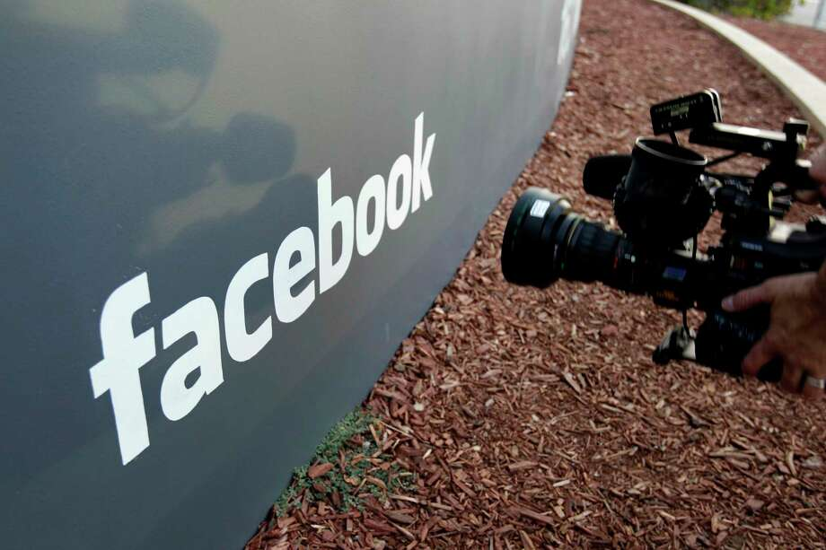 FILE - In this May 18, 2012, file photo a television photographer shoots the sign outside of Facebook headquarters in Menlo Park, Calif. A parliamentary committee report published Sunday, Feb. 17, 2019, has recommended that the United Kingdom government increase oversight of social media platforms like Facebook to better control harmful or illegal content. (AP Photo/Paul Sakuma, File) Photo: Paul Sakuma / Copyright 2018 The Associated Press. All rights reserved.