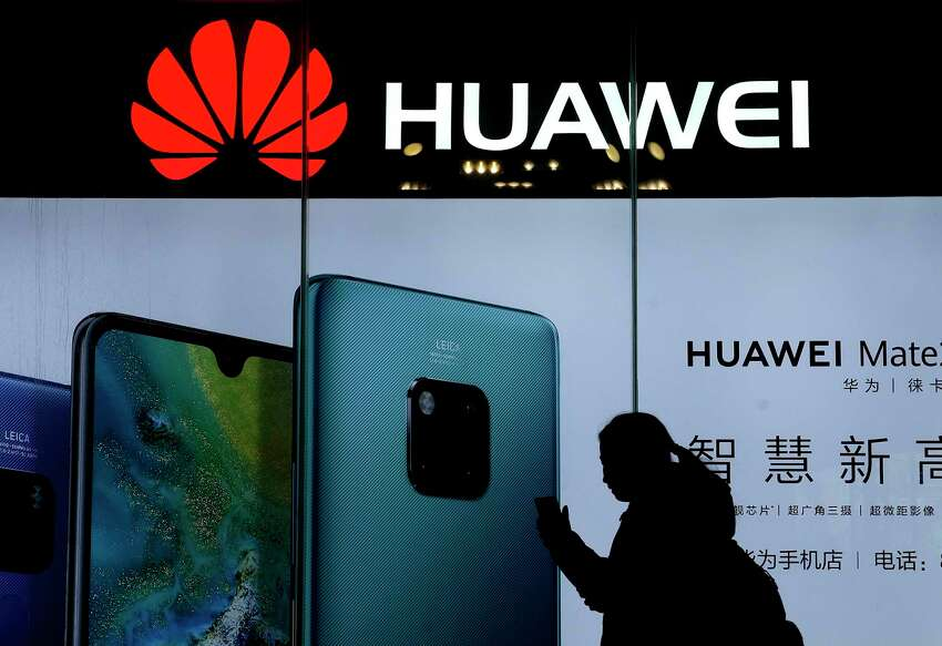 FILE - In this Dec. 11, 2018, file photo, a woman browses her smartphone as she walks by a Huawei store at a shopping mall in Beijing. China?s government has accused Washington of trying to block its industrial development after Vice President Mike Pence said Chinese tech giant Huawei and other telecom equipment suppliers are a security threat. (AP Photo/Andy Wong)