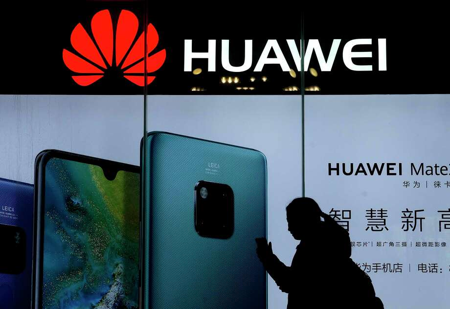 FILE - In this Dec. 11, 2018, file photo, a woman browses her smartphone as she walks by a Huawei store at a shopping mall in Beijing. China?s government has accused Washington of trying to block its industrial development after Vice President Mike Pence said Chinese tech giant Huawei and other telecom equipment suppliers are a security threat. (AP Photo/Andy Wong) Photo: Andy Wong / Copyright 2018 The Associated Press. All rights reserved.