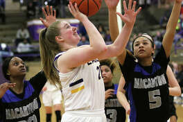 CM's Mackenzie Cato scores in the fourth quarter after beating Decatur MacArthur's Emari Brown (5) and Mariah Shores (5) to the basket Monday night in Taylorville.