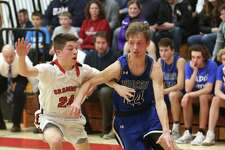 Old Lyme High School's Quinn Romeo dribbles up the court with Cromwell High School's Tyler Baldwin during the boys varsity basketball game in Cromwell on Monday, Feb. 18.