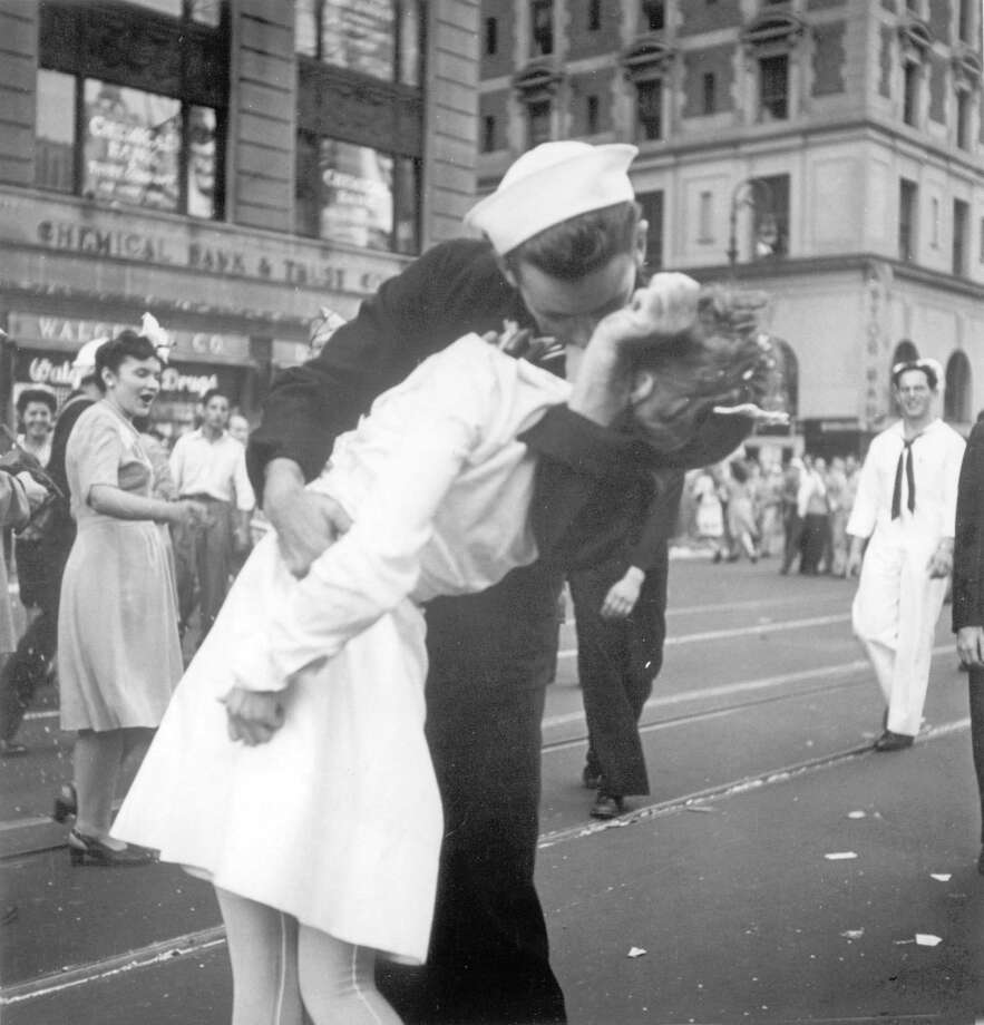 ADDS INFORMATION ABOUT PHOTOGRAPHER- FILE - In this Aug. 14, 1945 file photo provided by the U.S. Navy, a sailor and a woman kiss in New York's Times Square, as people celebrate the end of World War II. The ecstatic sailor shown kissing a woman in Times Square celebrating the end of World War II has died. George Mendonsa was 95. This image was taken by U.S. Navy photographer Victor Jorgensen. The photo is of the same moment that photographer Alfred Eisenstaedt captured and first published in Life magazine. (Victor Jorgensen/U.S. Navy, File) Photo: Victor Jorgensen / U.S. Navy