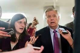 Sen. Lindsey Graham, R-S.C., speaks to journalists while walking to the Senate floor in January.