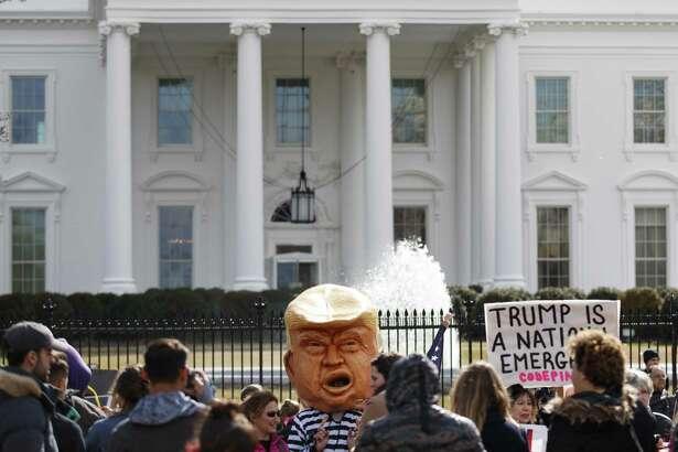 Una persona disfrazada del presidente Trump con uniforme de prisión y otras, se reúnen el lunes 18 de febrero de 2019, frente a la Casa Blanca en Washington.