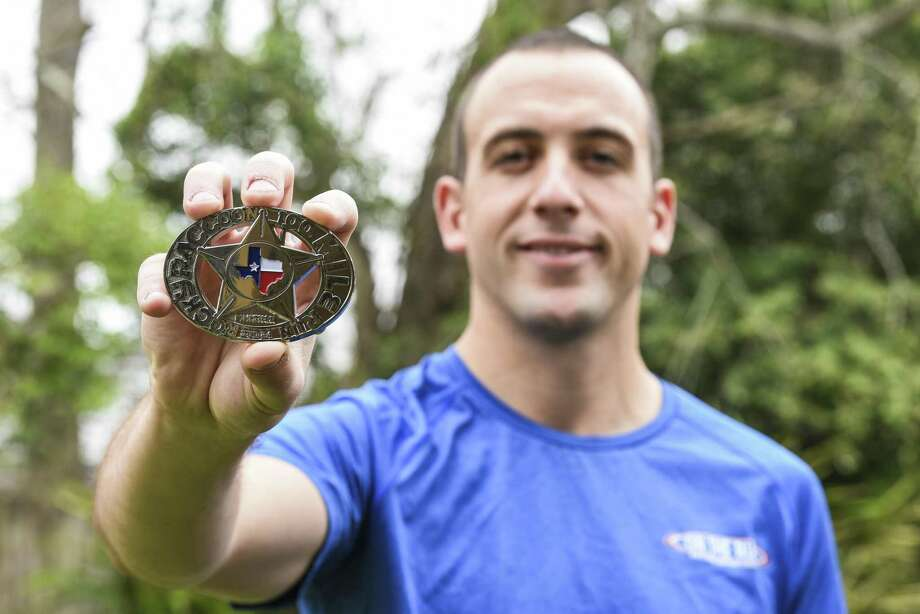 Joe Huyett poses in his house on Saturday with a buckle he was awarded after completing a 100 mile run. Photo taken on Saturday, 02/16/19. Ryan Welch/The Enterprise Photo: Ryan Welch / The Enterprise / ©Ryan Welch
