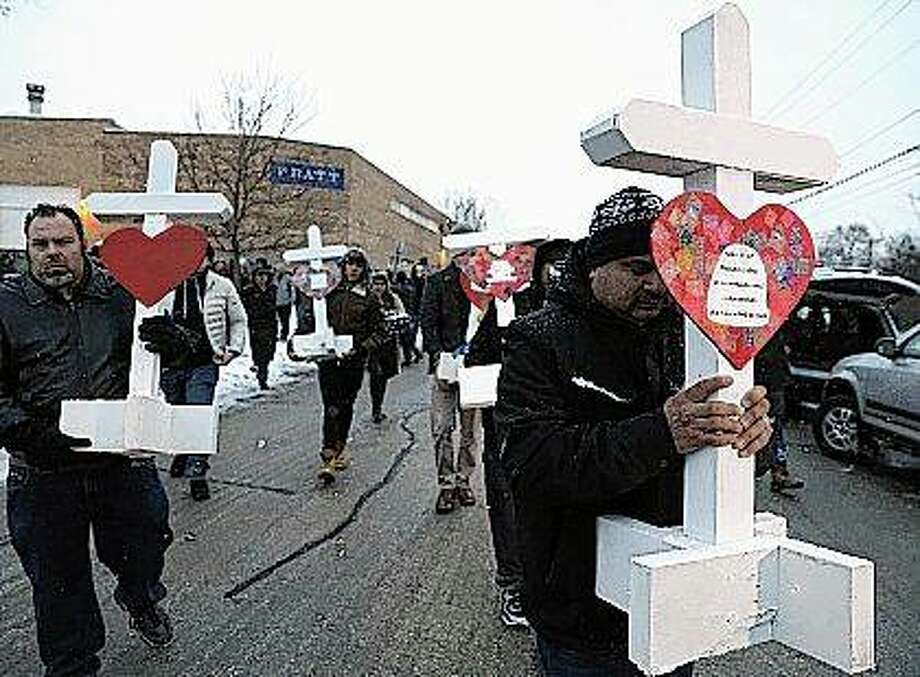 Casildo Cuevas holds a victim's cross as he walks to the Aurora police station after a makeshift memorial Sunday near Henry Pratt Co., a manufacturing company where several were killed Friday. Photo: Nam Y. Huh | AP