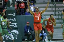 Tulane center Buay Koka (13) celebrates a score against Tulane in the second half of an NCAA college basketball game in New Orleans, Sunday, Feb. 17, 2019. Houston won, 85-50. (AP Photo/Matthew Hinton)