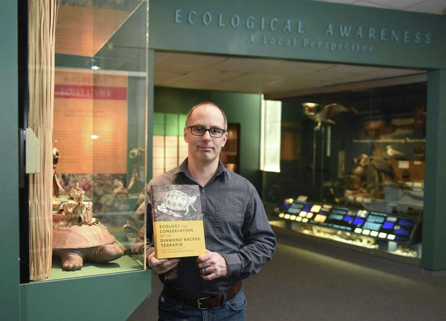"Collections Manager Tim Walsh poses with ""Ecology and Conservation of the Diamond-Backed Terrapin,"" a book in which he is featured, at the Bruce Museum. Walsh's writing is featured in the chapter ""Conservation through Environmental Education."" Photo: Tyler Sizemore / Hearst Connecticut Media / Greenwich Time"