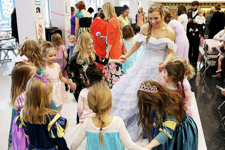 "Morgan Allen, a senior at Edwardsville High School and member of the Health Occupations Club dressed in costume as Princess Elsa from Disney's ""Frozen,"" leads a group of little princesses in a dance on Sunday at the fourth annual Princess Tea Party fundraising event at the EHS commons. The event raised approximately $1,200 for students to attend the HOSA state competition March 13-15 in Springfield."