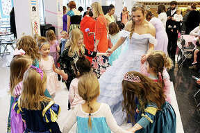 """Morgan Allen, a senior at Edwardsville High School and member of the Health Occupations Club dressed in costume as Princess Elsa from Disney's """"Frozen,"""" leads a group of little princesses in a dance on Sunday at the fourth annual Princess Tea Party fundraising event at the EHS commons. The event raised approximately $1,200 for students to attend the HOSA state competition March 13-15 in Springfield."""