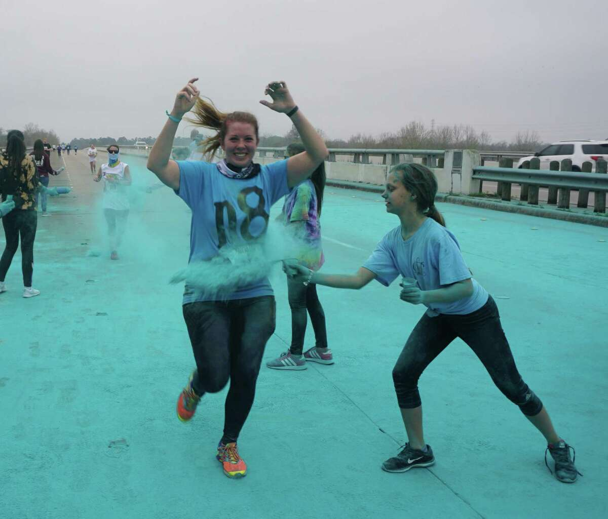 Catherine Olano of Humble and one of her daughters, Victoria, shower a runner with teal at the 28th Bridge Fest on Feb. 16, 2019 in Kingwood, TX. They are volunteers at the event along with members of the National Charity League's Lake Houston chapter, a philanthropic mother-daughter group.