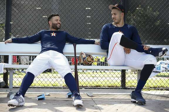Houston Astros players Jose Altuve, left, and Carlos Correa chat while waiting to take the field for live batting practice at Fitteam Ballpark of The Palm Beaches on Day 6 of spring training on Tuesday, Feb. 19, 2019, in West Palm Beach.