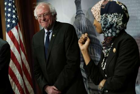U.S. Rep. Ilhan Omar (D-MN)  (R) and Sen. Bernie Sanders (I-VT) (L) share a moment during a news conference on prescription drugs January 10, 2019 at the Capitol in Washington, DC. Sanders announced Tuesday he would be running again for president. (Alex Wong/Getty Images/TNS)