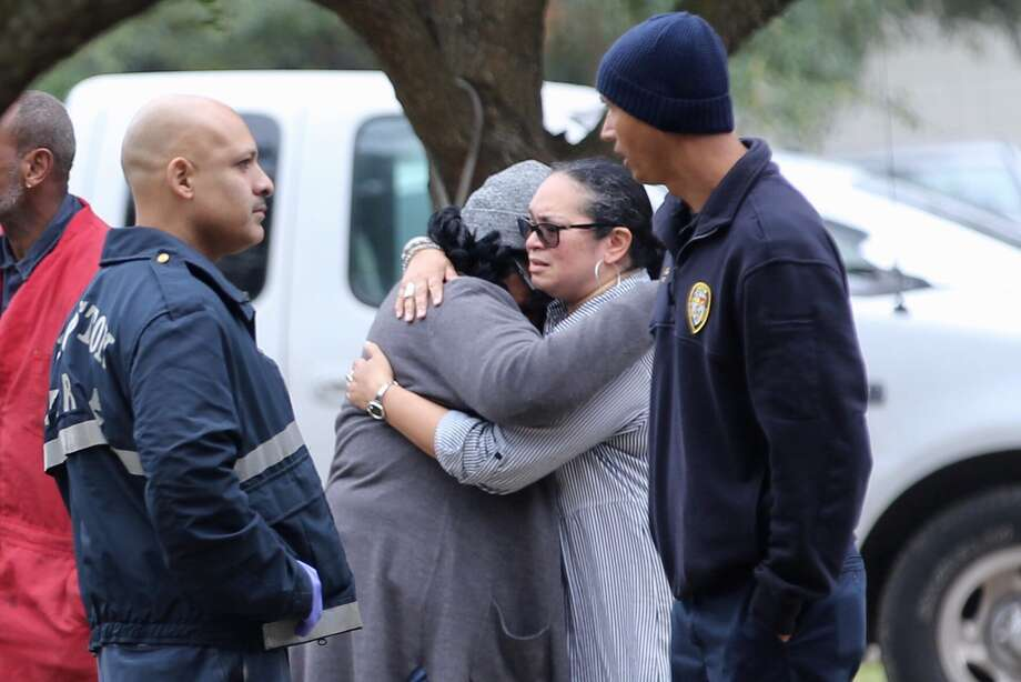 People hug down the street from where police investigate a scene where two men were found dead at a home in south Houston, Tuesday, Feb. 19, 2019. Photo: Mark Mulligan / 2019