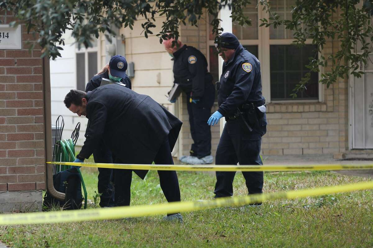Investigators search the scene two men found dead within a home in south Houston, Tuesday, Feb. 19, 2019.