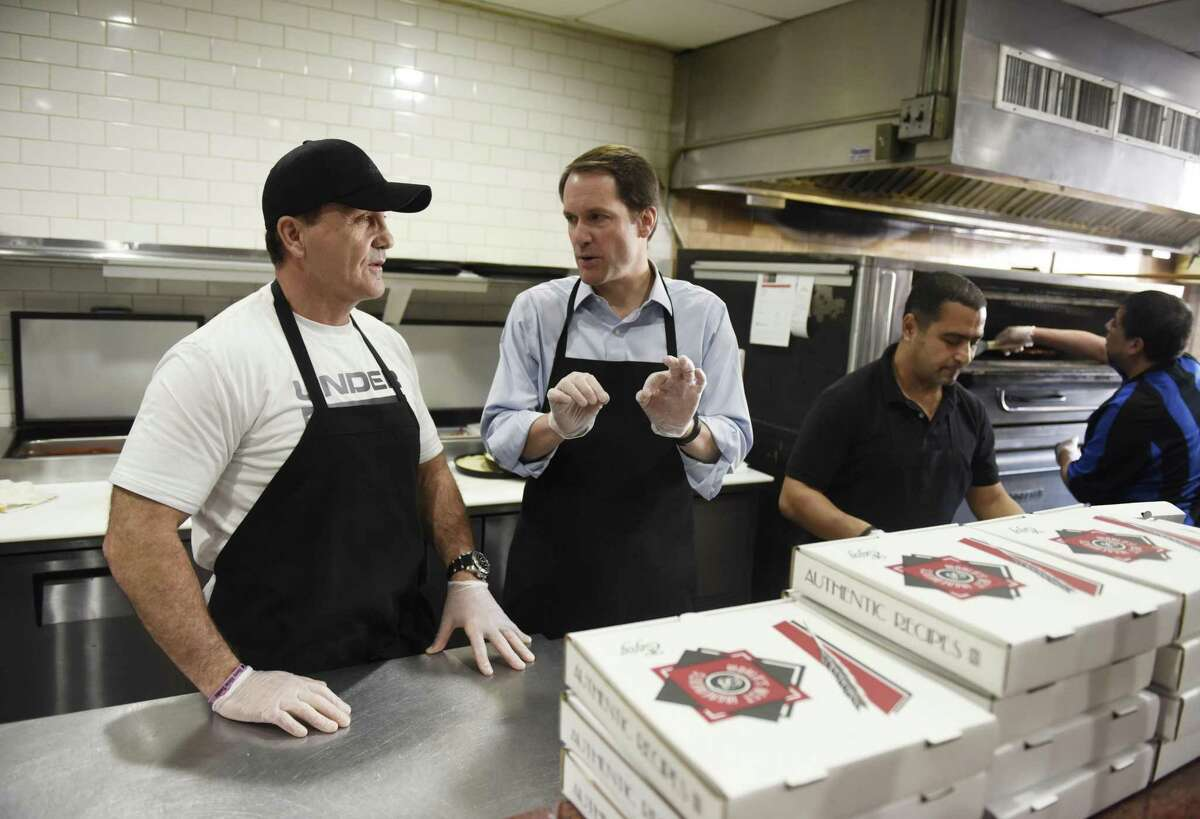 """Business owner Harry Zopounidis, left, and U.S. Rep. Jim Himes chat after making a pizza at Pappa's Pizzeria in Stamford, Conn. as part of the """"Jim on Your Job"""" series at Tuesday, Feb. 19, 2019. U.S. Rep. Himes made and delivered a pizza while chatting with the owner and employees at the family restaurant that's been in operation since the 1960s."""