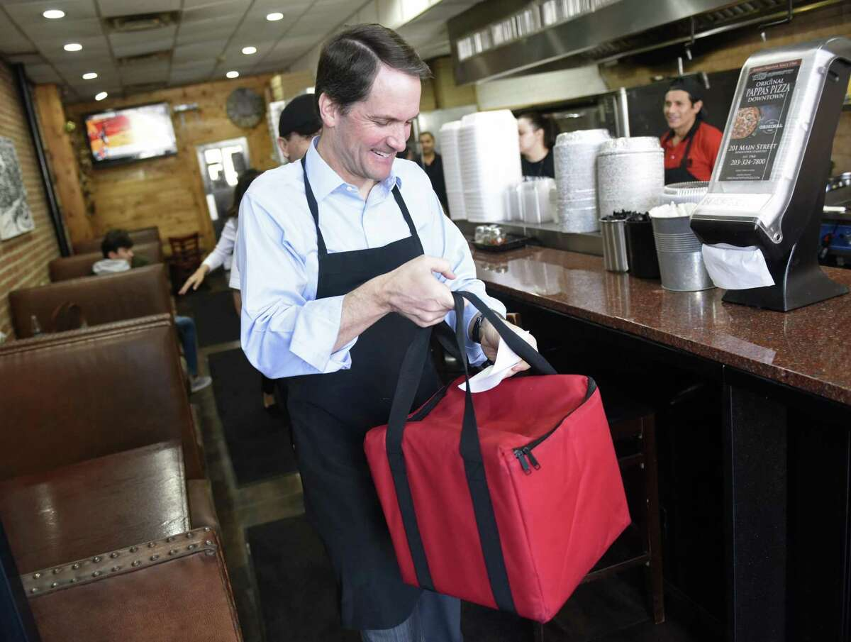 """U.S. Rep. Jim Himes gets ready to deliver a pizza from Pappa's Pizzeria in Stamford, Conn. as part of the """"Jim on Your Job"""" series at Tuesday, Feb. 19, 2019. U.S. Rep. Himes made and delivered a pizza while chatting with the owner and employees at the family restaurant that's been in operation since the 1960s."""
