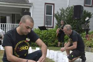 Raghib Allie-Brennam, vice president of The Heroin and Opiate Awareness Project (HERO) lights a luminaries with the name of a person who died from their addiction during the groups annual vigil to raise awareness of overdoses. Friday, August 31, 2018, at United Methodist Church, Bethel, Conn.