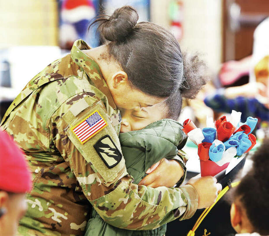 Sgt. Kyra Jones, who just returned home from a year-long deployment to Kuwait, gives a hug Tuesday to her daughter Raquel Jones, a second-grade student at Alton's West Elementary School. Jones, who is attached to the 155th Armored Brigade Combat Team in the Mississippi National Guard, surprised her two daughters in the school's cafeteria. Students in Raquel's class made the paper bouquet of flowers, right, but didn't know who they were actually for. Photo: John Badman   The Telegraph
