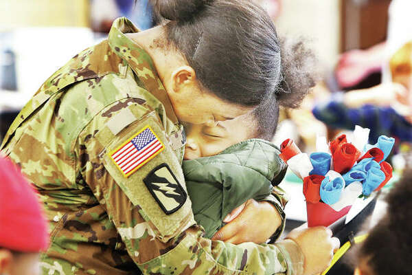 Sgt. Kyra Jones, who just returned home from a year-long deployment to Kuwait, gives a hug Tuesday to her daughter Raquel Jones, a second-grade student at Alton's West Elementary School. Jones, who is attached to the 155th Armored Brigade Combat Team in the Mississippi National Guard, surprised her two daughters in the school's cafeteria. Students in Raquel's class made the paper bouquet of flowers, right, but didn't know who they were actually for.