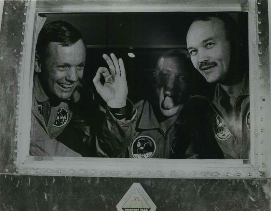In this photo dated Aug. 3, 1969, the Apollo 11 astronauts were in good spirits when they arrived at Ellington Air Force Base in Houston aboard their mobile quarantine facility. Neil Armstrong gives the A-OK sign. Buzz Aldrin hams it up for friends as Mike Collins grins. (World Book Science Service) / World Book Science Service