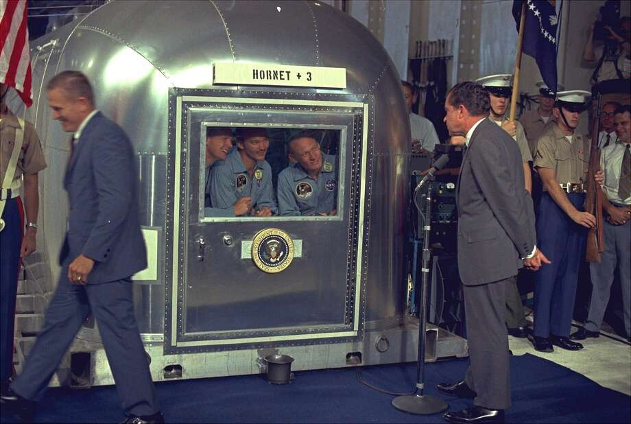 On July 24, 1969, President Richard Nixon views the Apollo 11 astronauts in the isolation unit aboard the USS Hornet after splashdown and recovery. The astronauts, from left, are: Neil Armstrong, Michael Collins and Buzz Aldrin. (Associated Press) / AP