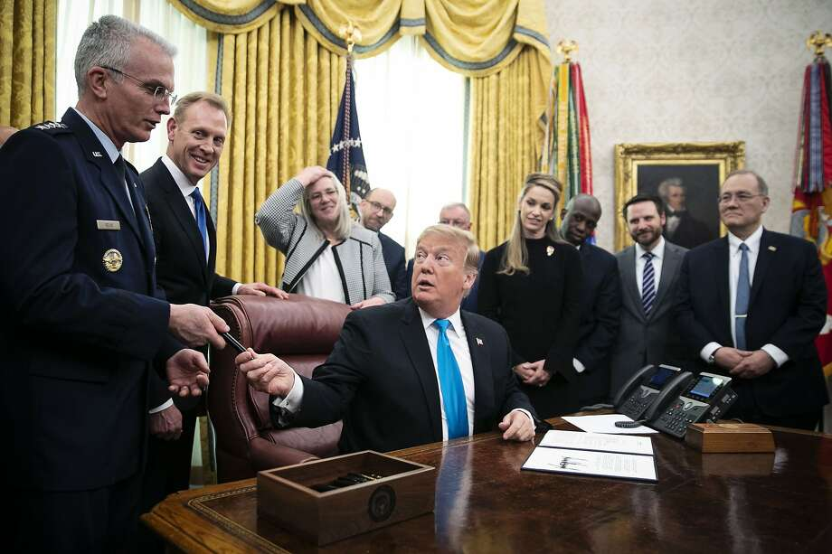 U.S. President Donald Trump, center, hands a pen to General Paul Selva, vice chairman of the Joint Chiefs of Staff, left, after signing Space Policy Directive 4 during a ceremony in the Oval Office of the White House in Washington, D.C., U.S., on Tuesday, Feb. 19, 2019. Trump signed a directive to establish a U.S. Space Force, saying that it needed to be formed because adversaries are in space.
