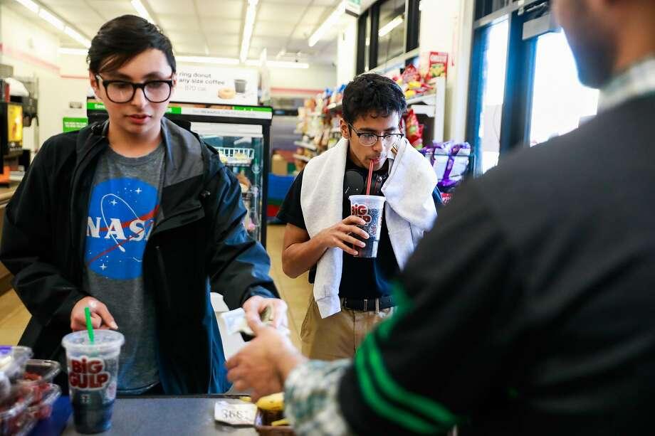 Carlos Ramirez (left) and Josue Llamas buy Big Gulp sodas at a 7-Eleven on Mission Street in San Francisco. Legislators will consider banning such big sugary drinks. Photo: Gabrielle Lurie / The Chronicle