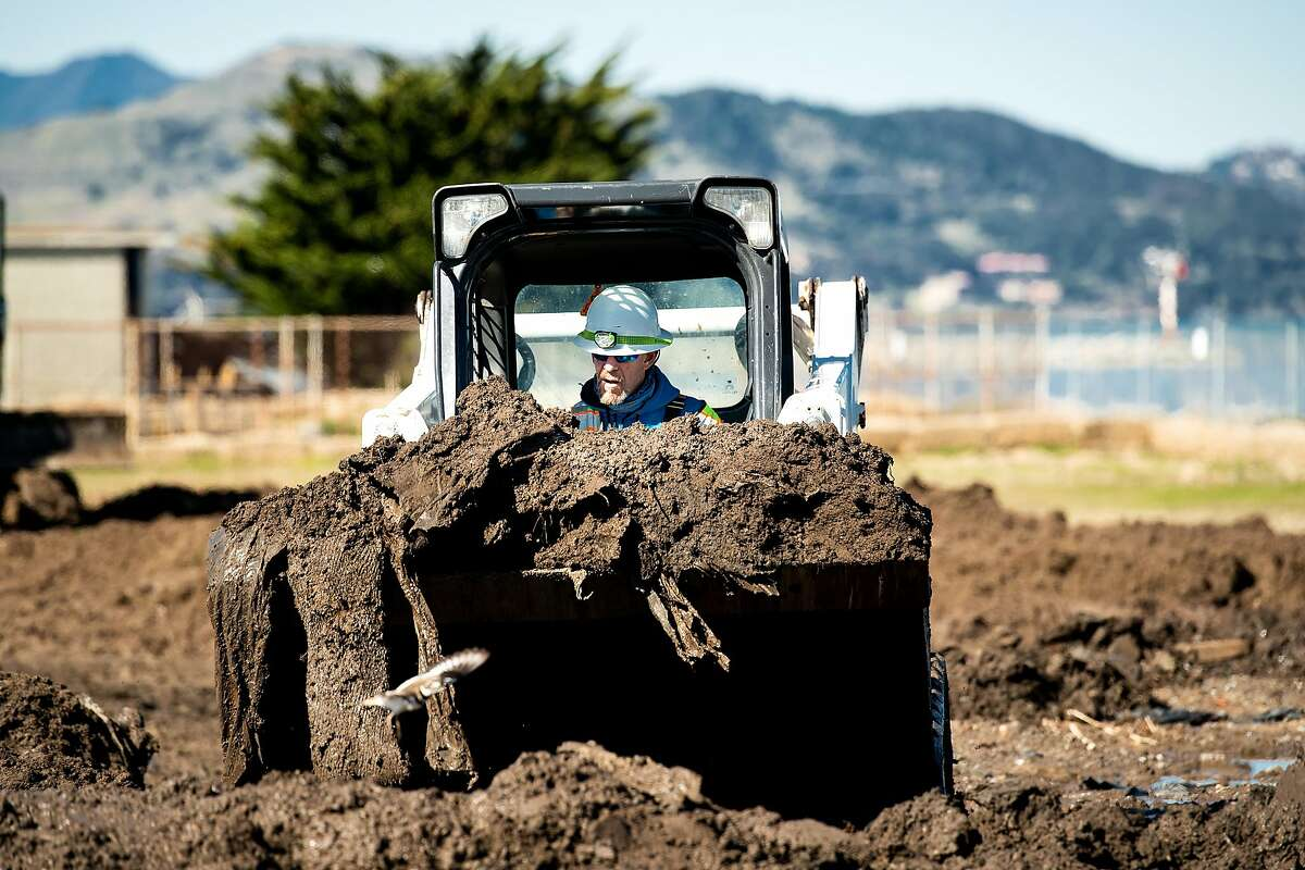 Workers prepare soil for radiation testing on Treasure Island on Tuesday, Feb. 19, 2019, in San Francisco, Calif. The parcel, gated off with radiation warning signs, sits near the Treasure Island Waste Water Treatment Plant along Avenue M.