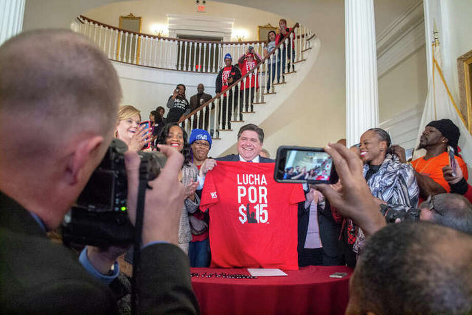 """Gov. J.B. Pritzker shows off a """"Fight for $15"""" shirt given to him by advocates at a bill signing event for Senate Bill 1 at the Governor's Mansion on Tuesday in Springfield. Pictured, the shirt is a Spanish version of the """"Fight for $15"""" slogan. Illinois' minimum wage will reach $15 hourly over the next six years. Photo: Jerry Nowicki 