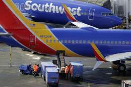 FILE- In this Feb. 5, 2019, file photo Southwest Airlines planes are loaded at Seattle-Tacoma International Airport in Seattle. Federal officials have told Southwest Airlines to fix the way it calculates the weight of luggage loaded on flights after finding frequent mistakes. Southwest said Tuesday, Feb. 19, that it made improvements in its methods for calculating weight and the balance of loads during 2018. (AP Photo/Ted S. Warren, File)