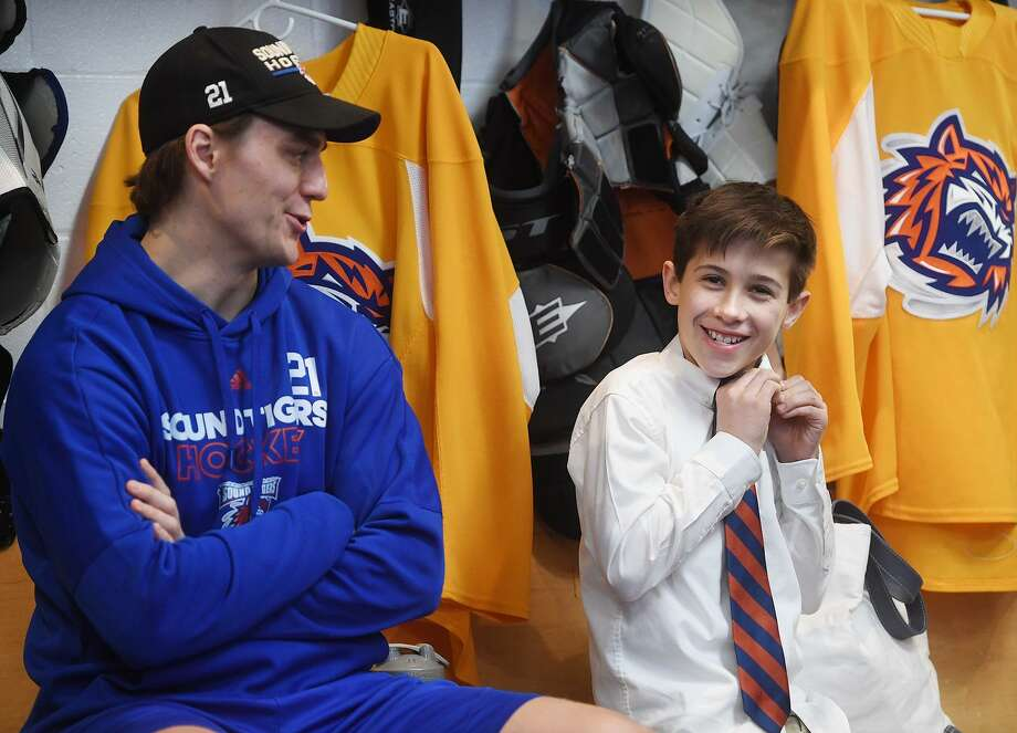 Kaden Symington, 12, of Ridgefield, puts on a tie as he sits with Bridgeport Sound Tigers team captain Ben Holmstrom before signing a one day contract with the team during a Make-A-Wish visit at the Webster Bank Arena in Bridgeport, Conn. on Tuesday, February 19, 2019. Photo: Brian A. Pounds / Hearst Connecticut Media / Connecticut Post