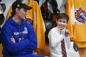 Kaden Symington, 12, of Ridgefield, puts on a tie as he sits with Bridgeport Sound Tigers team captain Ben Holmstrom before signing a one day contract with the team during a Make-A-Wish visit at the Webster Bank Arena in Bridgeport, Conn. on Tuesday, February 19, 2019.