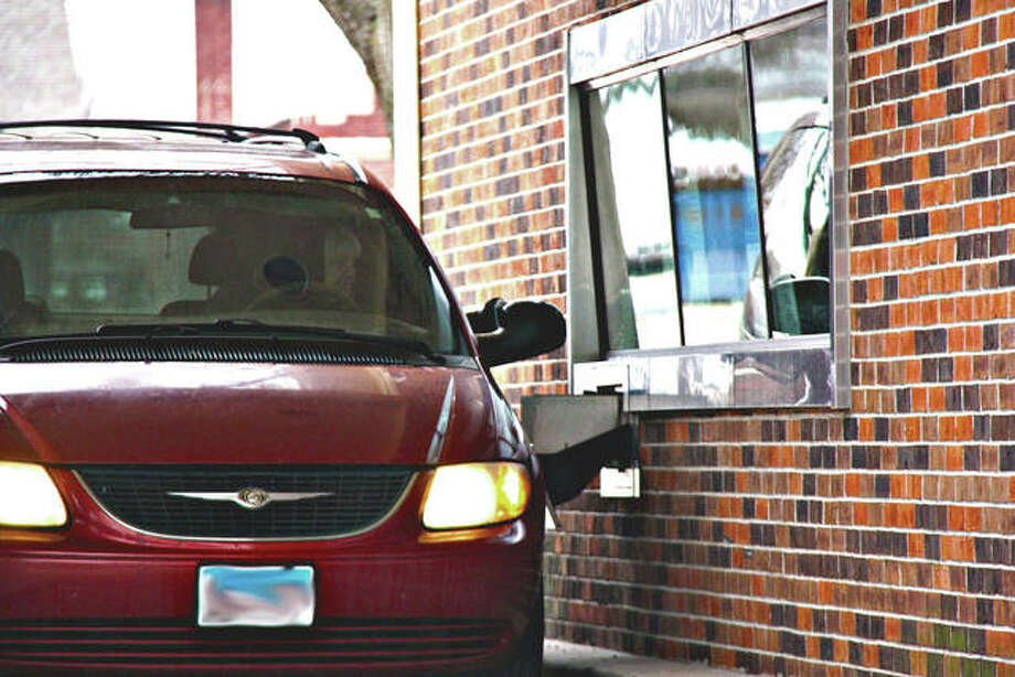 A drive-up customer reaches toward the bank window at the end of a transaction Tuesday at the U.S. Bank Midtown branch in Edwardsville. The branch will permanently close on Friday. Photo: Charles Bolinger | The Intelligencer