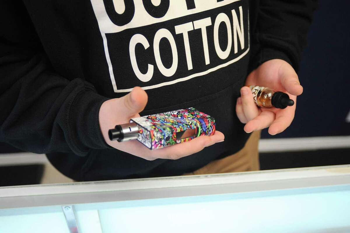 Joe Walsh, of Stamford Vaporium, shows off his personal vape and current flavor choice, fried oreo, on Thursday, Feb. 18, 2016.