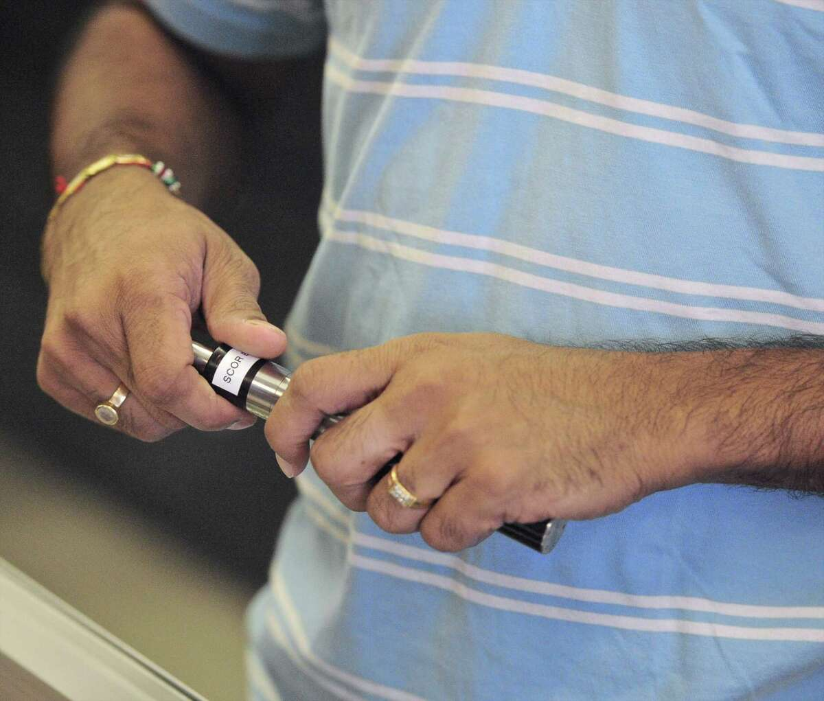 Twilight Vapor owner Saiyam Shah changes the flavored vape liquid for a customer to sample on Tuesday. State lawmaker's are calling for new regulations on vaping. August 30, 2016, in Danbury, Conn.