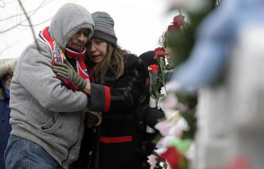 People attend at a makeshift memorial Sunday, Feb. 17, 2019, in Aurora, Ill., near Henry Pratt Co. manufacturing company where several were killed on Friday. Authorities say an initial background check five years ago failed to flag an out-of-state felony conviction that would have prevented a man from buying the gun he used in the mass shooting in Aurora. Photo: Nam Y. Huh, AP