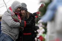 People attend at a makeshift memorial Sunday, Feb. 17, 2019, in Aurora, Ill., near Henry Pratt Co. manufacturing company where several were killed on Friday. Authorities say an initial background check five years ago failed to flag an out-of-state felony conviction that would have prevented a man from buying the gun he used in the mass shooting in Aurora.