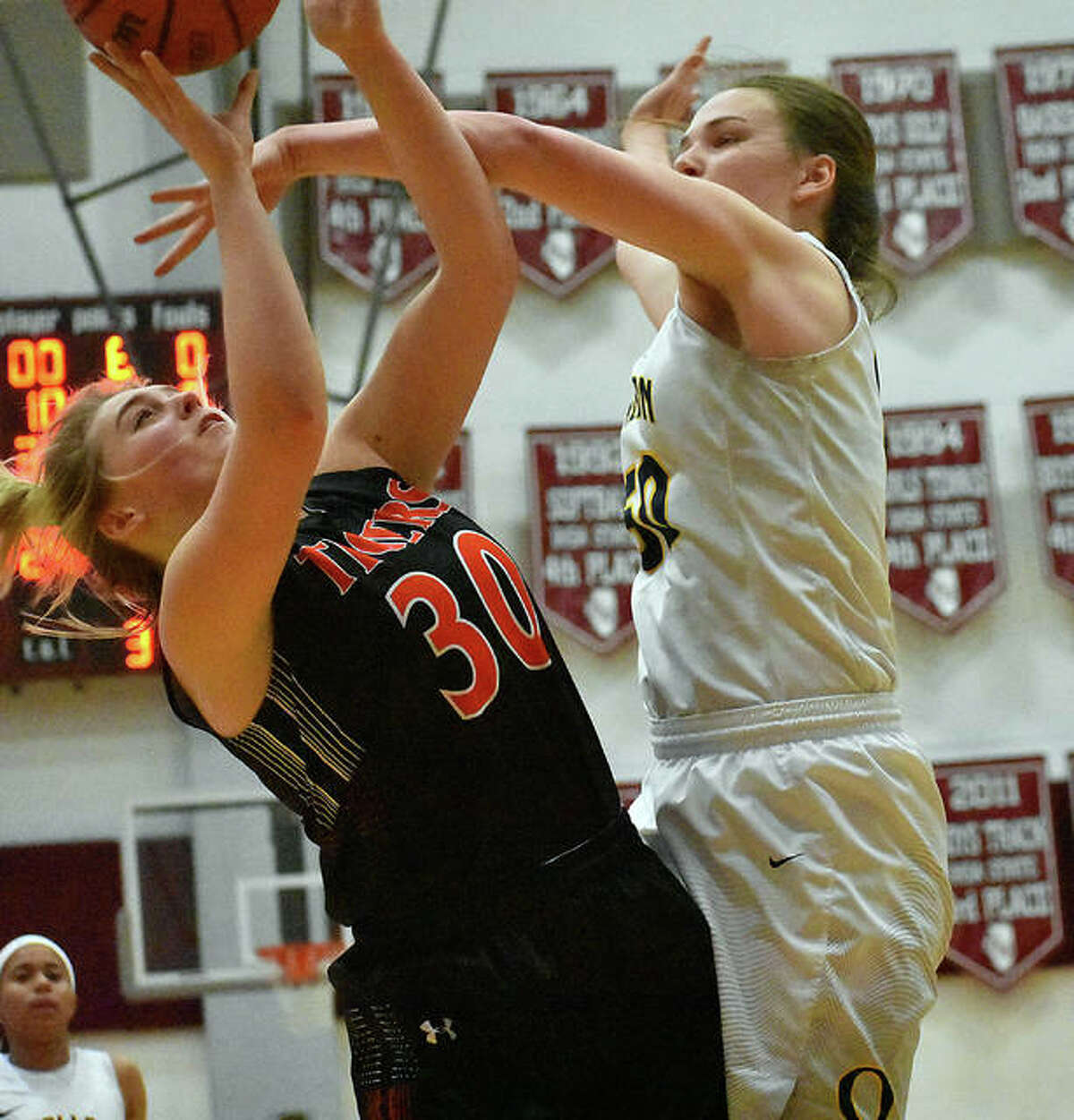 Edwardsville forward Morgan Hulme, left, is fouled as she goes up for a shot in the fourth quarter.