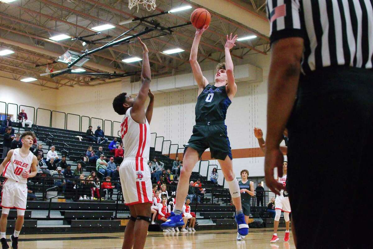 Clear Springs' Kyle Burt (0) puts up a shot over Dawson's Lorenzo Waddy (23) Tuesday, Feb. 19 at Alvin High School.