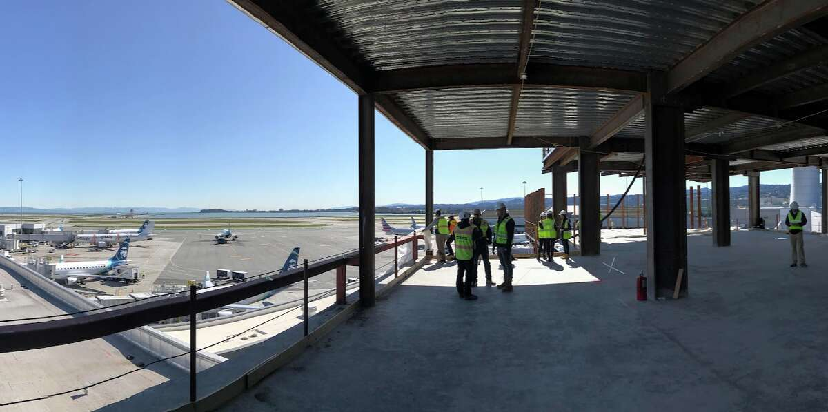 After exiting the elevator, guests walk along a wall of windows on the left overlooking the ramp and runways