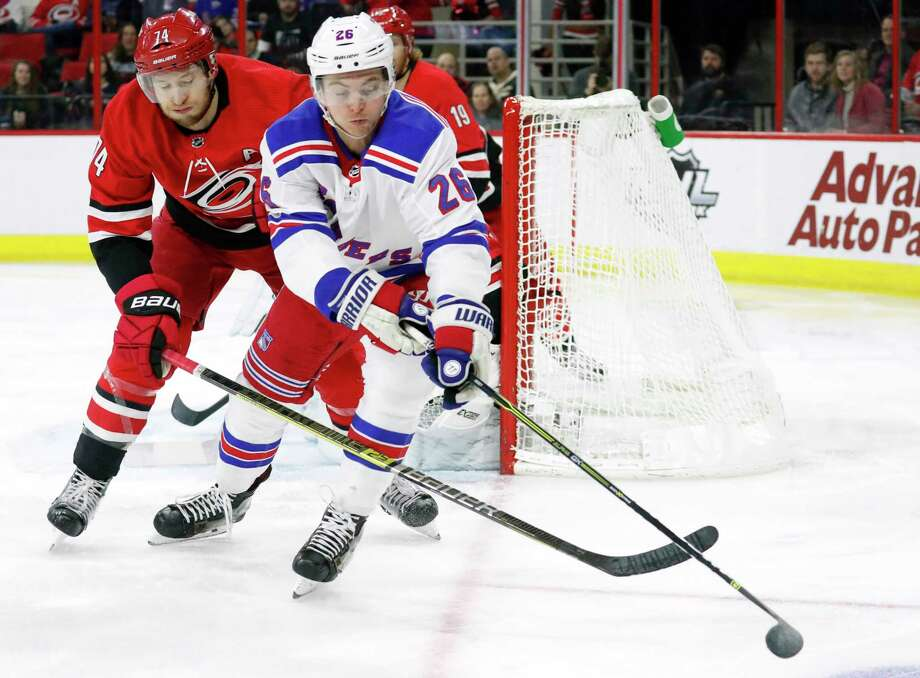 Carolina Hurricanes' Jaccob Slavin, left, and New York Rangers' Jimmy Vesey, right,  vie for the puck during the first period of an NHL hockey game in Raleigh, N.C., Tuesday, Feb. 19, 2019. (AP Photo/Chris Seward) Photo: Chris Seward / Copyright 2019 The Associated Press. All rights reserved