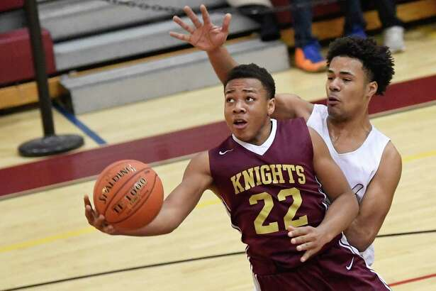 Bishop Gibbons' Rodney Parker (22) scores against Watervliet's Elijah Chambers (35) during a boys' Section II Class B high school basketball game Tuesday, Feb. 19, 2019, in Watervliet, N.Y. (Hans Pennink / Special to the Times Union)