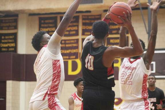 Keith Oliver (10) finds himself trapped by a pair of North Shore players Tuesday night. The Mustangs pressured the ball all night long in the front court, hoping to score some easy points.